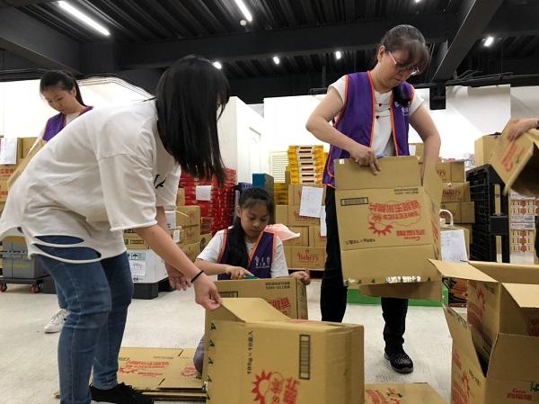 大小志工同心協力協助食物裝箱